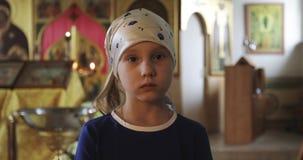 El retrato de la niña en una bufanda y un vestido azul está rogando en la iglesia almacen de metraje de vídeo