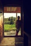 el retrato de la niña se coloca cerca de la puerta en la puesta del sol Fotos de archivo