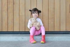 El retrato de la ni?a linda se sienta y abrazando a Teddy Bear contra la pared de madera del tabl?n foto de archivo