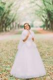 El retrato de la novia rubia feliz en la boa blanca del vestido y de la piel en carril en el otoño parquea fotografía de archivo