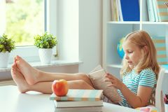 El retrato de la pequeña colegiala divertida que se relaja lee el libro en la tabla en sitio en casa imagenes de archivo