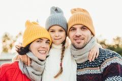 El retrato de la pequeña muchacha adorable lleva el sombrero hecho punto y el suéter se coloca entre los padres, los abraza La mu imagenes de archivo