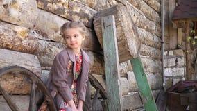 El retrato de la pequeña muchacha bonita que se colocaba delante de la casa de madera rural vieja se vistió en traje tradicional  almacen de metraje de vídeo