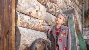 El retrato de la pequeña muchacha bonita que se colocaba delante de la casa de madera rural vieja se vistió en traje tradicional  metrajes