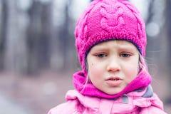El retrato de la pequeña muchacha caucásica linda en rosa hizo punto el sombrero que lloraba, siendo trastornada o perdida en un  foto de archivo