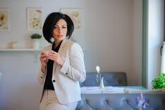 El retrato de la señora hermosa del negocio tiene un breake del coffe Foto de archivo libre de regalías