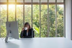 El retrato de la señora soñadora relajada acertada del negocio está descansando en su lugar de trabajo y café de las bebidas, par foto de archivo