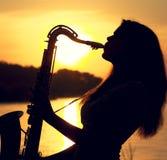 El retrato de la silueta de una mujer joven que toca hábilmente el saxofón en la naturaleza que le da la paz de la tranquilidad Imagen de archivo