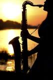El retrato de la silueta de una mujer joven que toca hábilmente el saxofón en la naturaleza que le da la paz de la tranquilidad Fotografía de archivo libre de regalías
