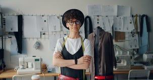 El retrato de la situación independiente del diseñador de la mujer en estudio con los brazos cruzó metrajes