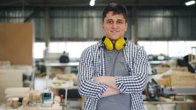 El retrato de la situación joven atractiva del carpintero en taller con los brazos cruzó almacen de video