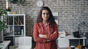 El retrato de la situación seria de la mujer joven en la oficina sola con los brazos cruzó almacen de metraje de vídeo