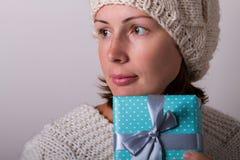 El retrato de la tenencia linda de la mujer joven envolvió el regalo Imagenes de archivo
