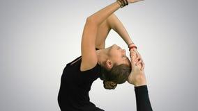 El retrato de la vista lateral de la mujer joven hermosa que hace yoga o los pilates ejercita Una actitud Legged de rey Pigeon, E metrajes