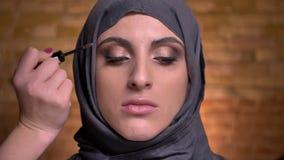 El retrato de las manos femeninas que cepillan las cejas de la mujer musulmán en hijab encendido bricken el fondo de la pared almacen de metraje de vídeo