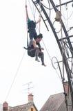 El retrato de las mujeres jovenes que entrenan en el trapecio para las acrobacias aéreas al aire libre muestra en el lugar princi Imagen de archivo