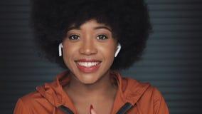 El retrato de los auriculares que llevan de la mujer afroamericana feliz joven, escucha la m?sica y el baile en la c?mara almacen de video