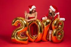 El retrato de muchachas bonitas emocionadas en la Navidad viste la presentación Imágenes de archivo libres de regalías