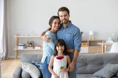 El retrato de padres felices abraza la presentaci?n con la hija linda imagenes de archivo