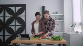 El retrato de pares de amor sonrientes en cocina, muchacha feliz con el individuo prepara la comida sana para la cena con las ver metrajes
