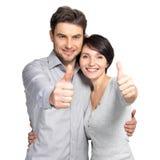El retrato de pares felices con los pulgares sube la muestra fotografía de archivo