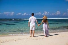 El retrato de pares felices, en la playa, lleva a cabo las manos, mar Foto de archivo libre de regalías