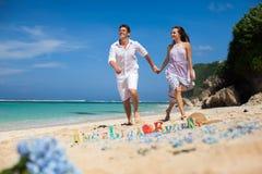 El retrato de pares felices, en la playa, lleva a cabo las manos, mar Imagenes de archivo
