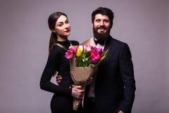 El retrato de pares jovenes en amor con el ramo de presentación de los tulipanes de la primavera se vistió en ropa clásica en bac Imagen de archivo libre de regalías