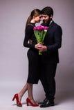 El retrato de pares jovenes en amor con el ramo de presentación de los tulipanes del lila se vistió en ropa clásica en backround  Fotografía de archivo