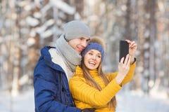 El retrato de pares jovenes sonrientes hace un selfie en un bosque en el invierno Foto de archivo libre de regalías