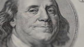 El retrato de presidente Benjamin Franklin en cientos billetes de dólar gira en macro almacen de video