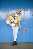 El retrato de un adolescente de moda que tocaba la guitarra contra la madera artesonó la pared Fotos de archivo libres de regalías