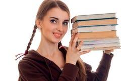 El retrato de un adolescente joven con las coletas ha aumentado en las manos de las miradas del libro en la cámara y la sonrisa Imagen de archivo