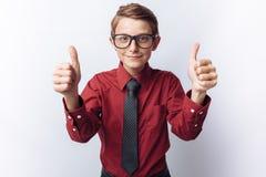 El retrato de un adolescente positivo en un fondo blanco, y las demostraciones clasifican, en camisa roja, la publicidad, inserci Foto de archivo