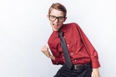 El retrato de un adolescente positivo y emocional, representa la alegría, fondo blanco, vidrios, camisa roja, tema del negocio, p Fotos de archivo libres de regalías