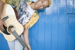 El retrato de un adolescente que tocaba la guitarra contra la madera artesonó la pared Fotografía de archivo