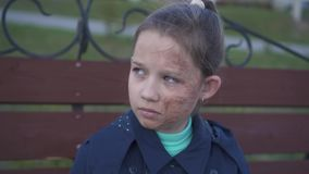 El retrato de un adolescente triste con la cara quemada oculta su cara debajo de una capilla almacen de metraje de vídeo
