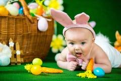El retrato de un bebé divertido lindo se vistió en oídos del conejito de pascua con los huevos Fotografía de archivo libre de regalías