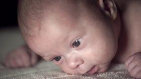 El retrato de un bebé recién nacido está intentando aumentar su cabeza que miente en su estómago almacen de video