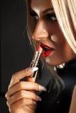 El retrato de un blonde joven hermoso ese pinta el lápiz labial rojo Imagen de archivo