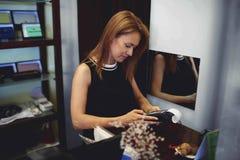 El retrato de un consultor atractivo de la mujer introduce crédito del código del PIN en máquina del lector de tarjetas mientras  Fotografía de archivo libre de regalías