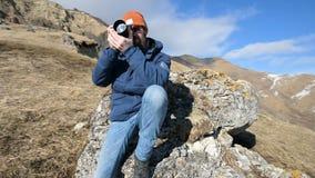 El retrato de un fot?grafo barbudo del viajero en gafas de sol y un casquillo se sienta en una roca con la c?mara del espejo en s almacen de metraje de vídeo