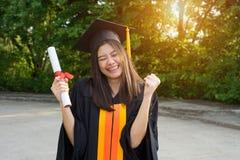 El retrato de un graduado femenino de la universidad lleva el vestido académico negro y el sombrero, sostiene el certificado del  imagen de archivo libre de regalías