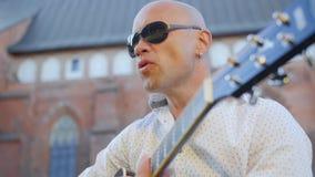 El retrato de un hombre adulto calvo en gafas de sol toca la guitarra y canta al aire libre Ci?rrese encima de tiro almacen de metraje de vídeo