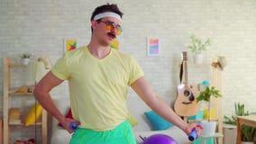 El retrato de un hombre atlético divertido en el estilo de 80s es pesas de gimnasia involucradas con y presentación en la cámara metrajes