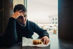 El retrato de un hombre barbudo joven que se sienta en el restaurante y los alimentos de preparación rápida puede comer no más Foto de archivo libre de regalías