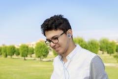 El retrato de un hombre egipcio joven urbano de moda escucha la música adentro Imagen de archivo libre de regalías