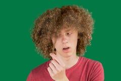 El retrato de un hombre europeo rizado joven asustó miradas en su pelo largo contra backgound verde sostiene un rizo del pelo con imagen de archivo libre de regalías