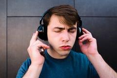El retrato de un hombre hermoso con los ojos se cerró y disfrutando de música en auriculares contra un fondo de la pared gris Foto de archivo