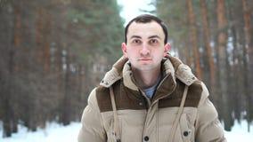 El retrato de un hombre joven en una chaqueta en el hombre del bosque se coloca en bosque del invierno almacen de video